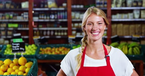 Portrait of smiling Caucasian female staff standing with hands on hip in grocery section of supermarket