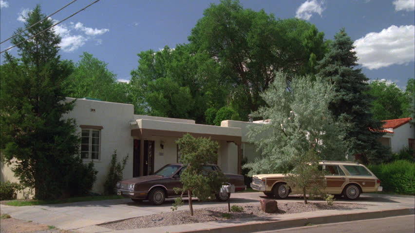 day left one story house stucco adobe style mid 1980s brown Buick Sedan cream tan station wagon 1 2 circle driveway, green trees