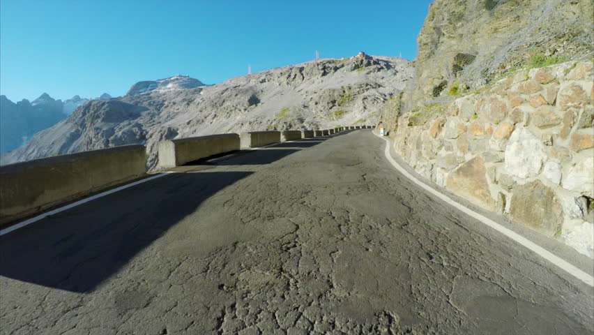 Driving through hairpin turns of Stelvio Pass, highest pass in the Alps on sunny summer day