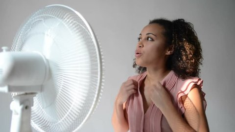 Black woman feeling hot and sitting in front of an electric fan to get some cool air on her face