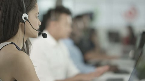 4K Mixed ethnicity customer service team taking calls in busy call centre. Shot on RED Epic.