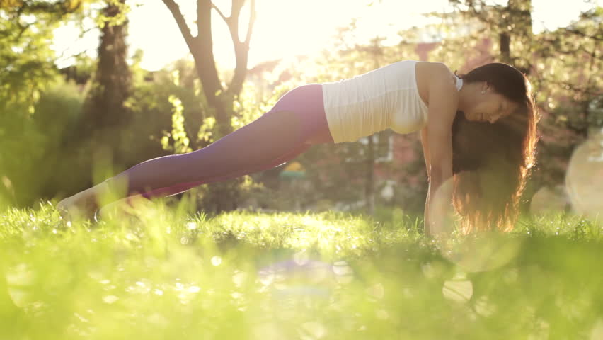 Ground angle shot of yoga and pilates exercises on the lawn at sunny morning. Athletic woman stretching on the meadow with green grass in the park