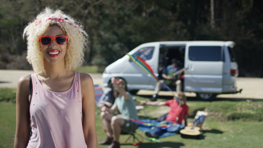 4k portrait of smiling hipster girl with friends in background at 4k portrait of smiling hipster girl with friends in background at music festival campsite shot voltagebd Image collections