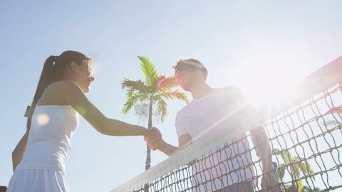 Tennis players handshake thanking each other for a game of tennis on court outdoor. Couple or mixed double tennis partners after playing tennis outside in summer. Happy young people, woman and man.