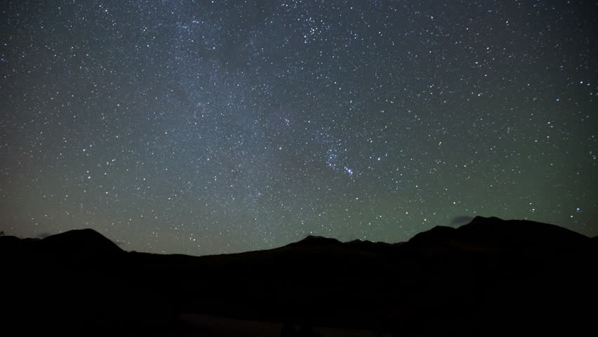 4K time lapse of the Milky Way Galaxy stars moving across the night sky above silhouetted La Sal mountains and scattered clouds on a mostly clear evening in Utah #20387473