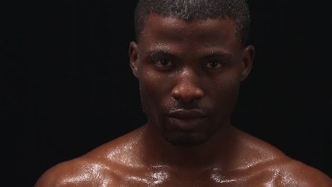 Studio shoot footage of wet Afro-American man posing for photographer on black background. Professional model looking at camera without any emotions. Handsome Afro American man.
