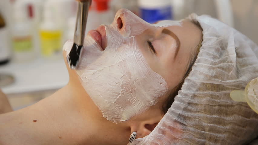 Beautiful woman with facial mask at beauty salon.Applying facial mask at woman face at beauty salon.Spa therapy for young woman receiving facial mask at beauty salon.Beautician does face mask.Spa