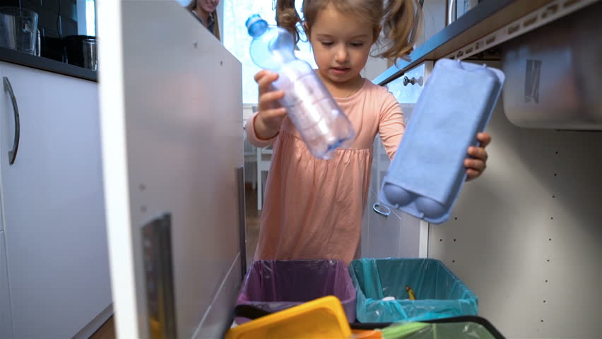 Little girl drops the trash into kitchen recycling bin. Slow motion.