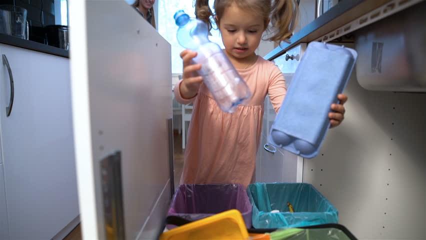 Little girl drops the trash into kitchen recycling bin. Slow motion. | Shutterstock HD Video #20439763