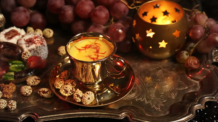 Traditional Oriental Sweets on Vintage Moroccan Tray. Cup of Saffron Masala Tea with spices. Gala dinner by candlelight. Arab, African, Turkish, Persian and Indian silver dishes (Kitchen Utensils)