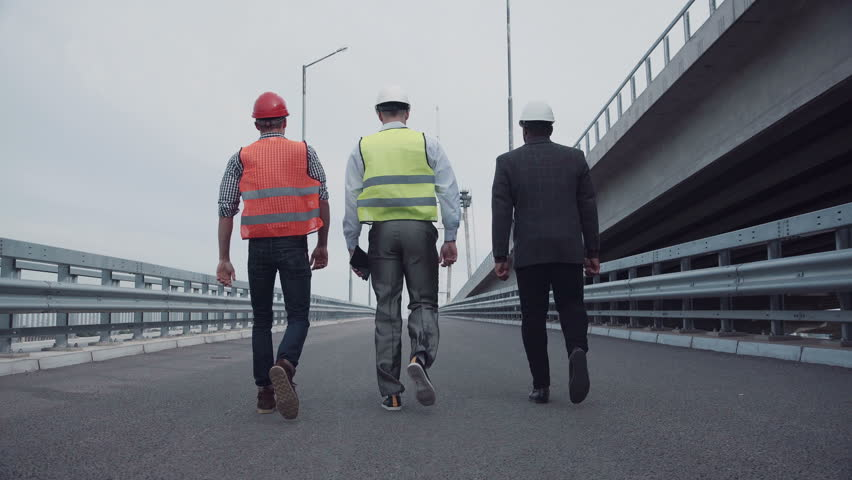 4K shot of Diverse group of three male construction engineers in white hard hats with reflective jackets walking on highway ramp. Rear view on road along bridge.