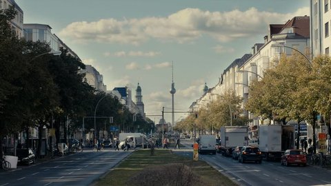 A street in Berlin, with a view of TV tower, many cars, people, moving clouds.