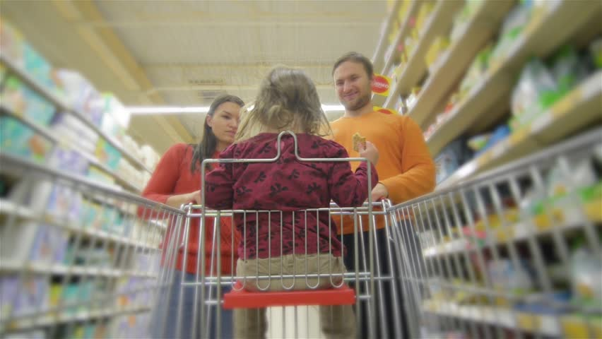 Beautiful young parents and their cute little daughter are smiling while choosing food in the supermarket. Girl is sitting in the shopping cart   Shutterstock HD Video #20534815