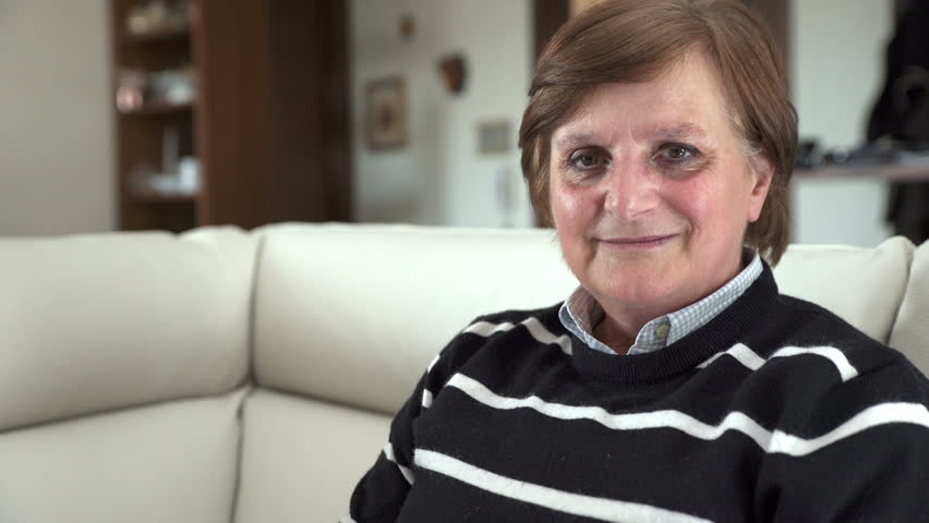Happy elderly woman on the couch smiling at the camera