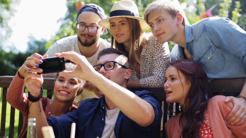 Leisure, party, technology, people and holidays concept - happy friends taking selfie with smartphone and gathering for dinner at summer garden party | Shutterstock HD Video #20553031
