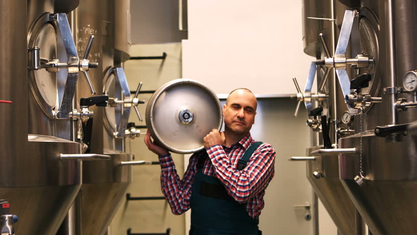 Slow motion of brewer carrying keg at brewery