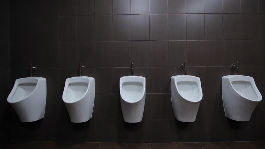 Urinals are fixed on a white wall, gray tiles on the walls, brown floor tiles, taps for urinals silver metal. survey conducted indoors under fluorescent light bulbs, front view. wide angle, static