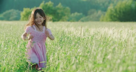 little Asian girl running on the green field and holds the hand of his father, slow motion