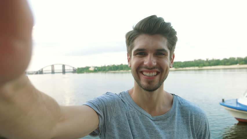 Cheerful selfie. Cheerful young man in shirt holding mobile phone and making photo of himself while standing in city river | Shutterstock HD Video #20648113