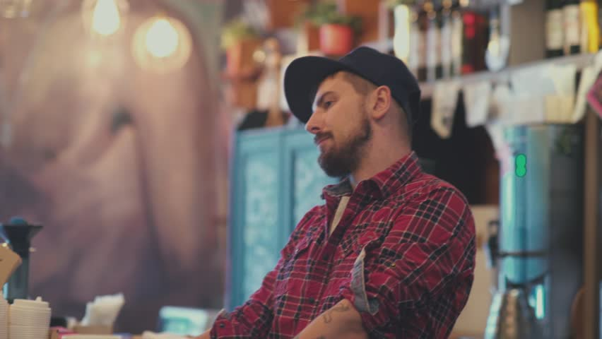 Portrait of a hipster. Portrait of a young man with a beard, wearing a cap and a red plaid shirt. Occupation barista. The modern city dweller. The rhythm of the city.