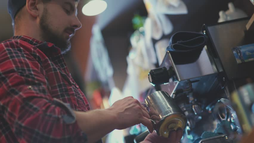 Barista at work. The process of making coffee. A glass of foaming milk. Barista cap and plaid shirt. Barista - nice young man with a beard. Preparing cups of espresso at a busy coffee shop.