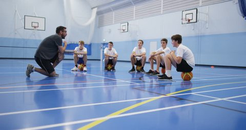 4k, A male coach talking to a group of teenage boys during a physical education class.