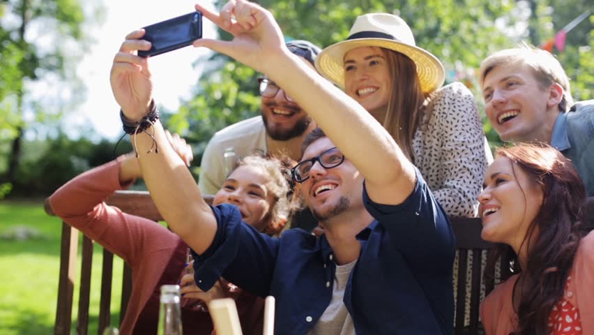 Leisure, party, technology, people and holidays concept - happy friends taking selfie with smartphone and gathering for dinner at summer garden party | Shutterstock HD Video #20705425