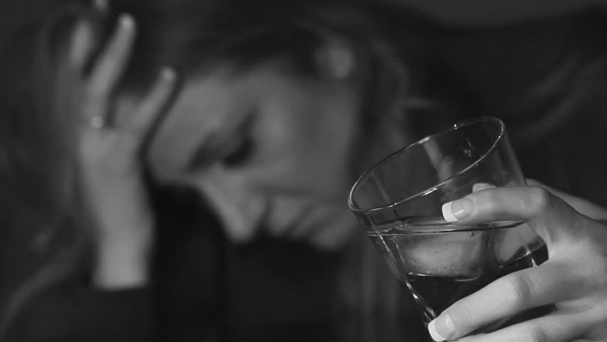 Young woman drinking alcohol. Glass in sharp focus. Shallow DOF. Black and white.