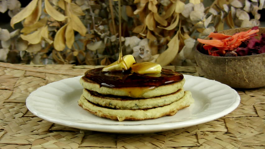 Pancakes With Dripping Maple Syrup (HD). Stack of pancakes with butter and Maple Syrup dripping slowly from above to melt the butter and cover the tower of flavor.
