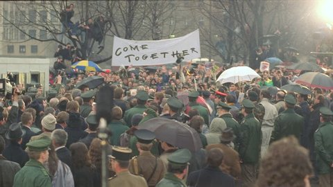 day down crowd celebrating near Berlin Wall, see photo flashes military soldiers, Come Together banner, light rain, umbrellas fall Berlin Wall, historical footage