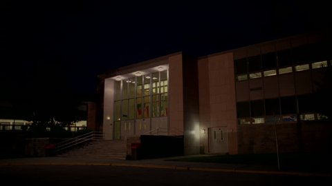 night Static tall lit two story high school building many windows stairs front Raked R