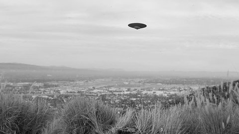 FLYING SAUCER CAUGHT ON FILM.  VINTAGE-LOOKING, BLACK & WHITE  FOOTAGE OF A UFO TRAVELING CAMERA RIGHT TO LEFT.