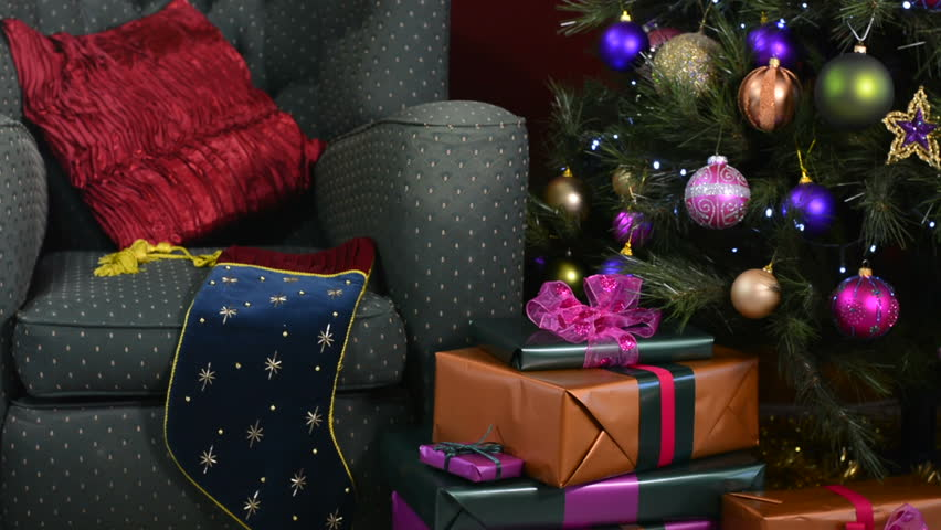 hd0011festive christmas scene with comfortable chair beside a christmas tree with jewel color decorations panning right close up - Jewel Colored Christmas Decorations