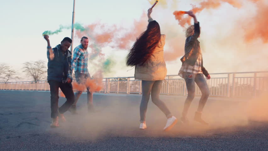 Four happy young mixed racial friends dancing on bridge in city at sunset in evening with colored smoke grenades. Urban environment