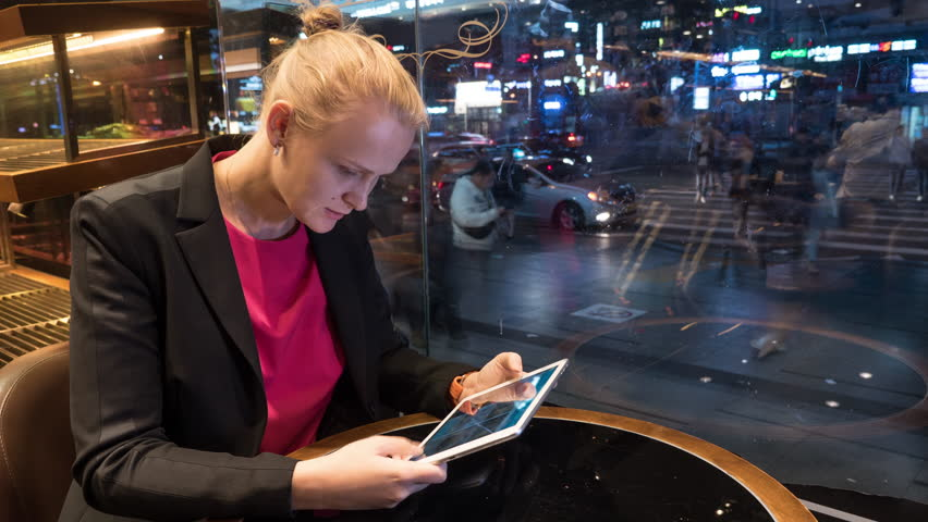 Cinemagraph - Young woman using tablet computer in the cafe in the evening, timelapse of people and traffic on the street outside. Seoul, South Korea