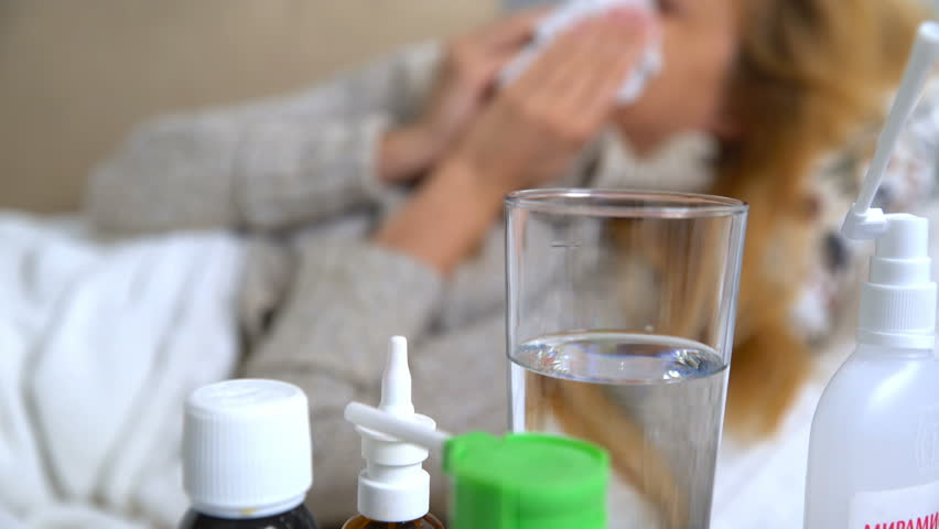A woman with fever and runny nose uses nasal spray and sneezes.