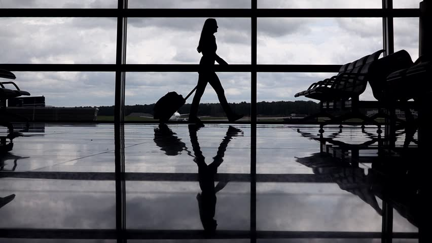 Female traveller silhouette, woman go against terminal window with trolley case, slow motion. Empty departure hall, full height passenger, polished floor reflect shadow contour. Cloudy sky outside