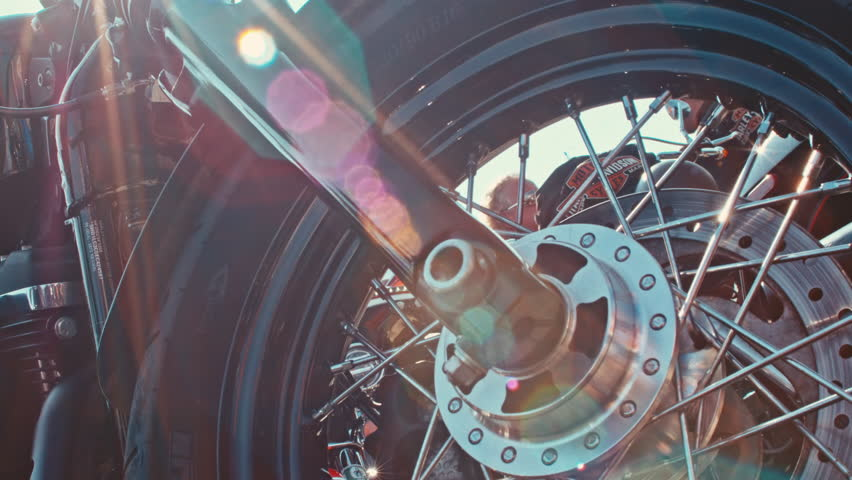 Close up of a motorcycle wheel and swing arm with beautiful bokeh / Europe's biggest Harley Davidson event 6-11 September 2016 (Faaker See/AUT) 4K editorial footage