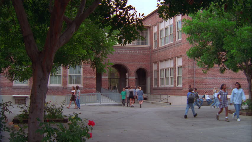 day Back ND 2 story brick Junior high school with arched entryway, school yard plaza area Students thru