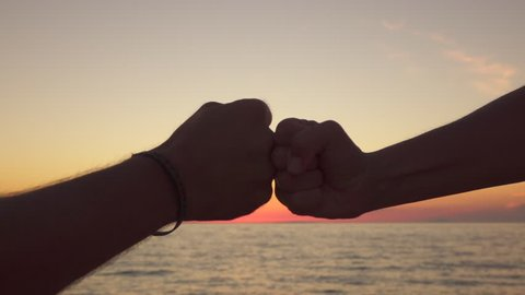 SLOW MOTION CLOSE UP: Two best friends meeting on stunning ocean shore, tapping gently fists together as symbol of giving respect and as a form of greeting. Man and woman celebrating success at sunset