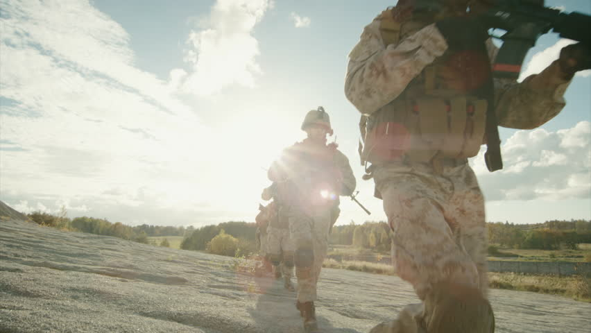 Squad of Fully Equipped and Armed Soldiers Running in Single File in the Desert. Slow Motion. Shot on RED EPIC Cinema Camera in 4K (UHD).