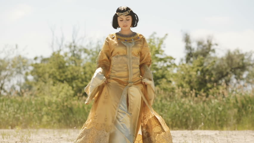 Fashion stylish beauty woman with black short haircut and professional make-up of Cleopatra. Girl walking in full lenght in golden dress outdoors in desert