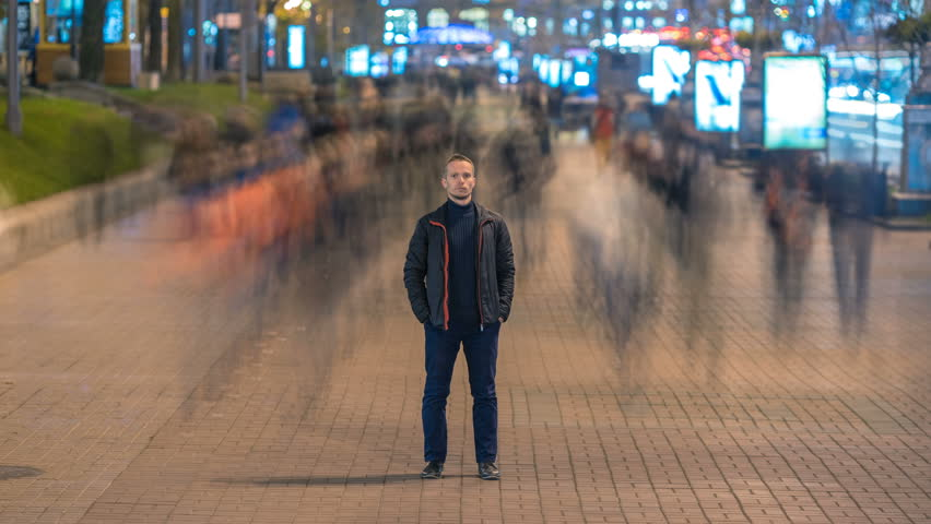 The man stand in the ghost-like crowd flow. Evening to night time. Time lapse