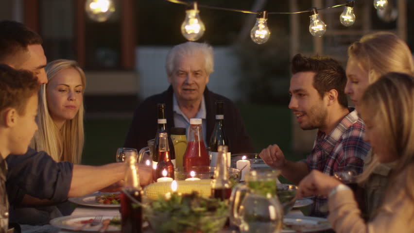 Group of People Sitting Around a Table, Eating, Communicating and Having Fun during Family Dinner. Shot on RED Cinema Camera in 4K (UHD).