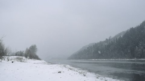 River in winter park. Winter landscape. Snow drifts on river bank. Winter river with fog. River bank covered with snow. Misty winter river. Snowy winter park. Trees covered by snow. Cold weather