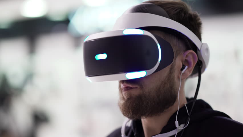 Bearded man uses VR-headset display with headphones for virtual reality game. UHD 4K