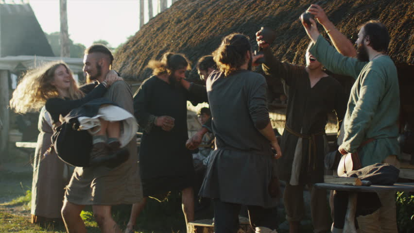 Dressed in Medieval Clothing Group of People Drinking, Dancing and Celebrating. Life of Civilian People at the Village. Medieval Reenactment. Shot on RED Cinema Camera in 4K (UHD).