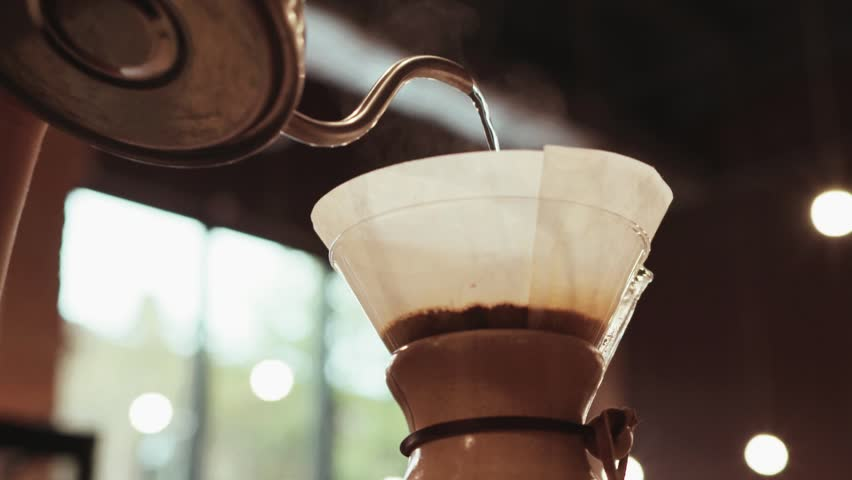 Close up of a barista making hand brewed coffee. Adding grinded coffee and pouring hot water. Baristas portrait. Inside shooting. Cafe atmosphere. Cafe activities. Restaurant activities. #20956324