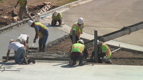 Construction workers pour concrete mix from cement mixer and trowel flat
