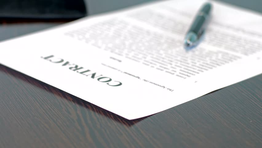 A contract waiting to be signed, the contract lies on a table with a fountain pen, no people, generic contractual language, panning move | Shutterstock HD Video #20996053